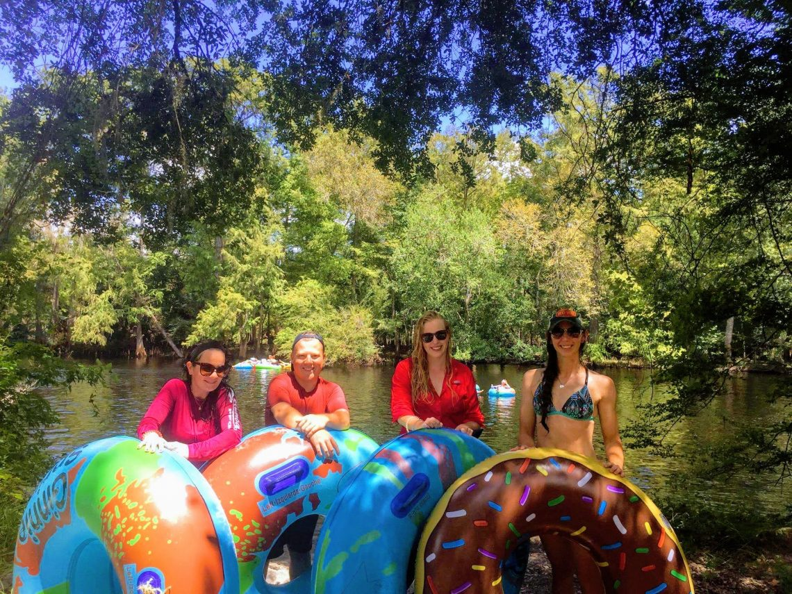 Tubers pose with their floats in front of the river.
