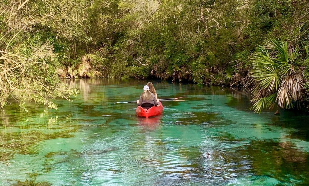 Two kayakers paddling down the Weeki Wachee River.