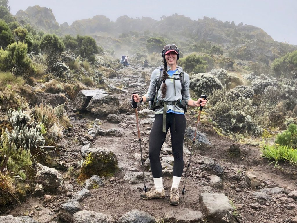 Hiker takes a break to show some of the clothes she packed from her Kilimanjaro packing list.