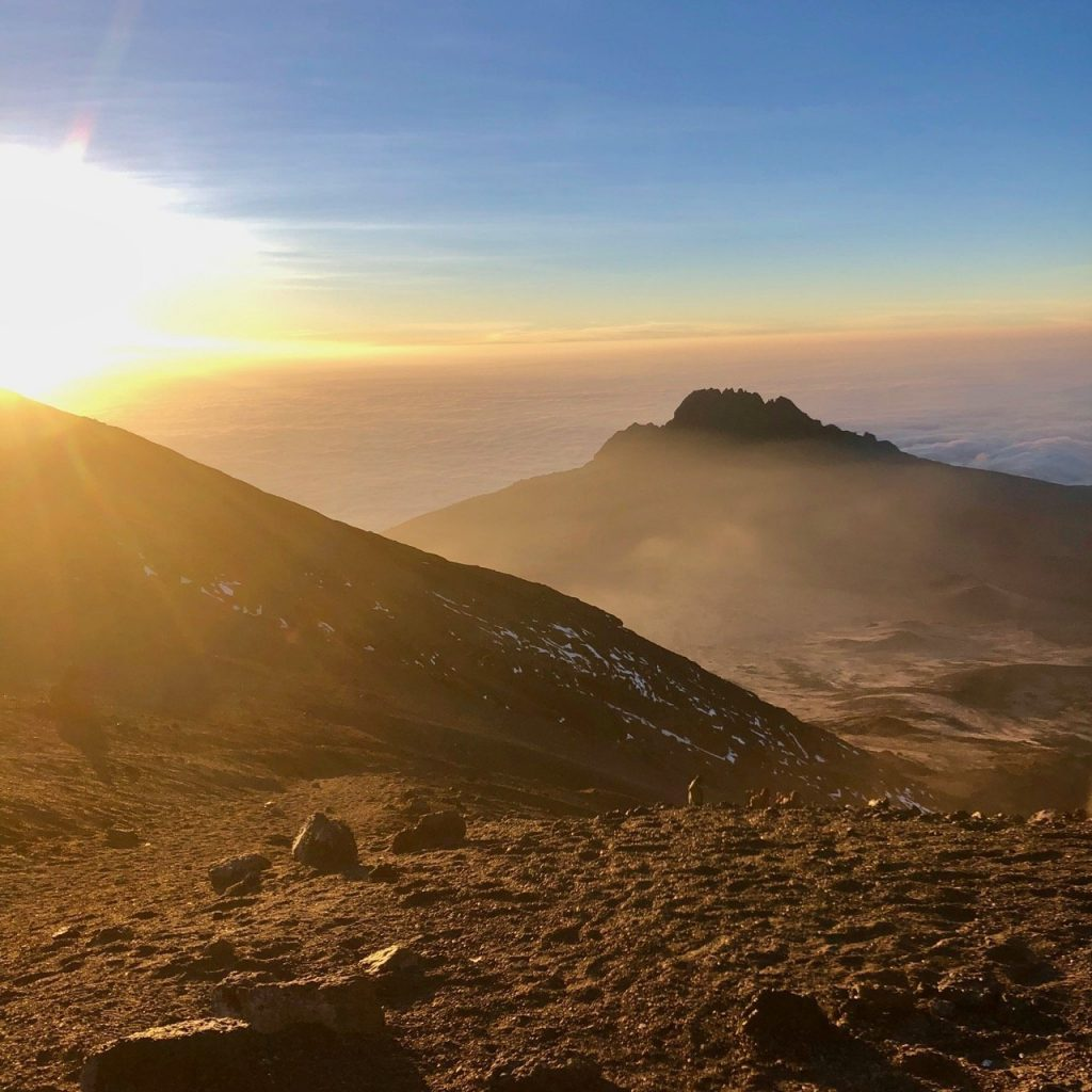 A view from Stella Point on Mount Kilimanjaro as the sun rises above the clouds.