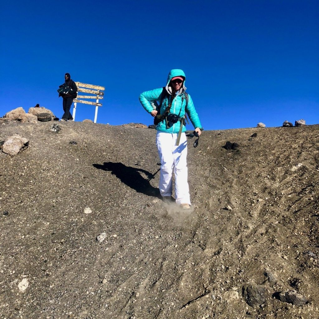 A hiker coming down from the summit of Kilimanjaro sliding down the scree, or loose rocks.