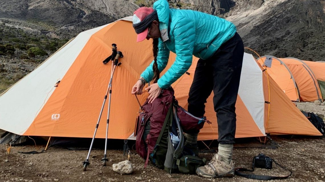 Hiker sorts through backpack and other gear while climbing Kilimanjaro