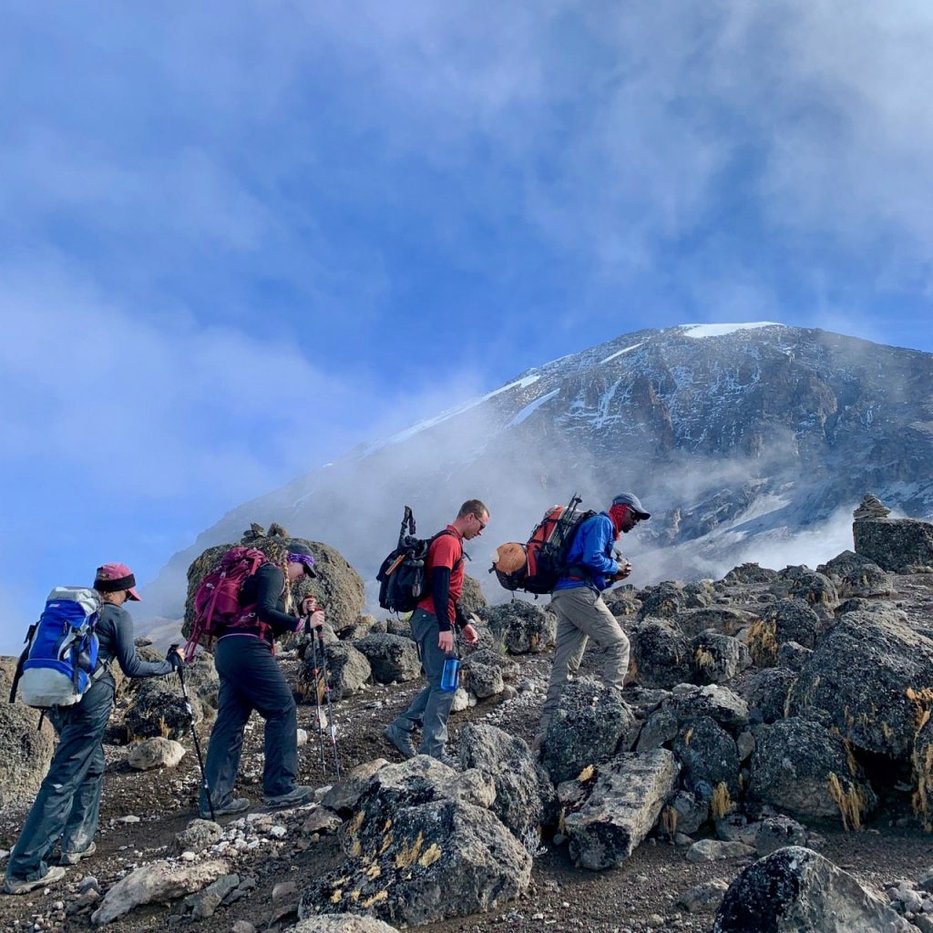 Hikers climb with Kilimanjaro in the background.