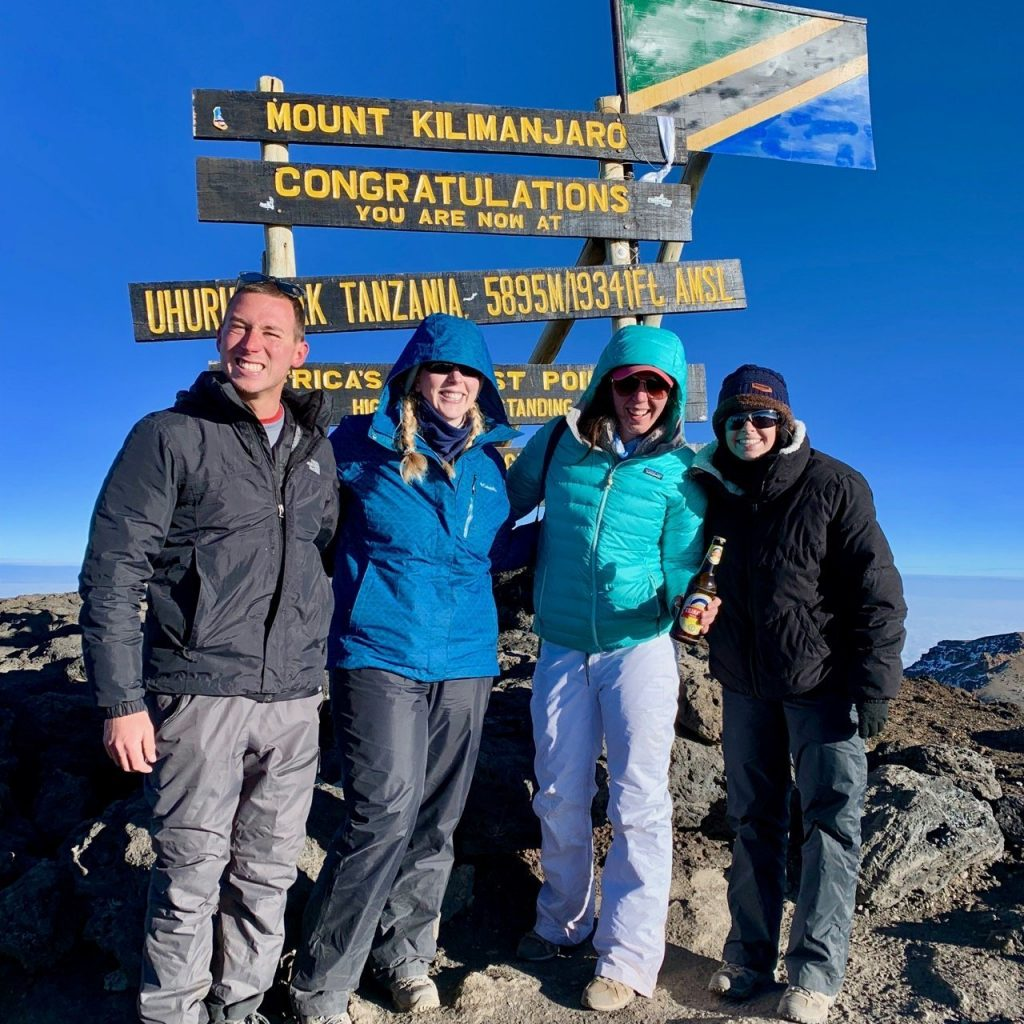 Celebrating a successful summit to Uhuru Peak in front of the congratulations sign on Mount Kilimanjaro