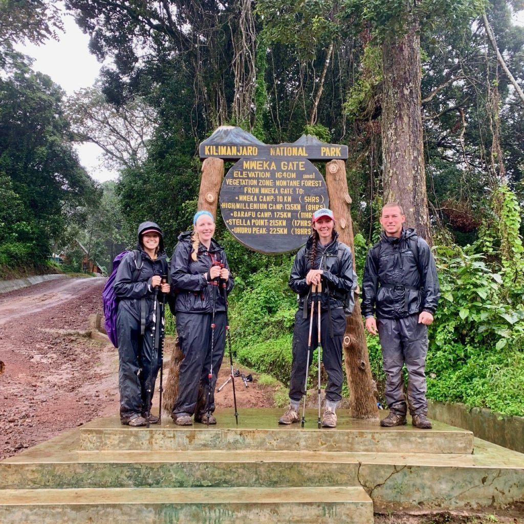 Hikers take a photo in front of the Mweka gate sign.