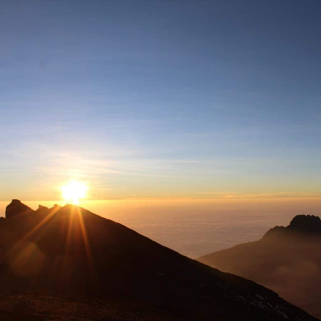 The sun rises as seen from just before Stella Point, summit day on Kilimanjaro.