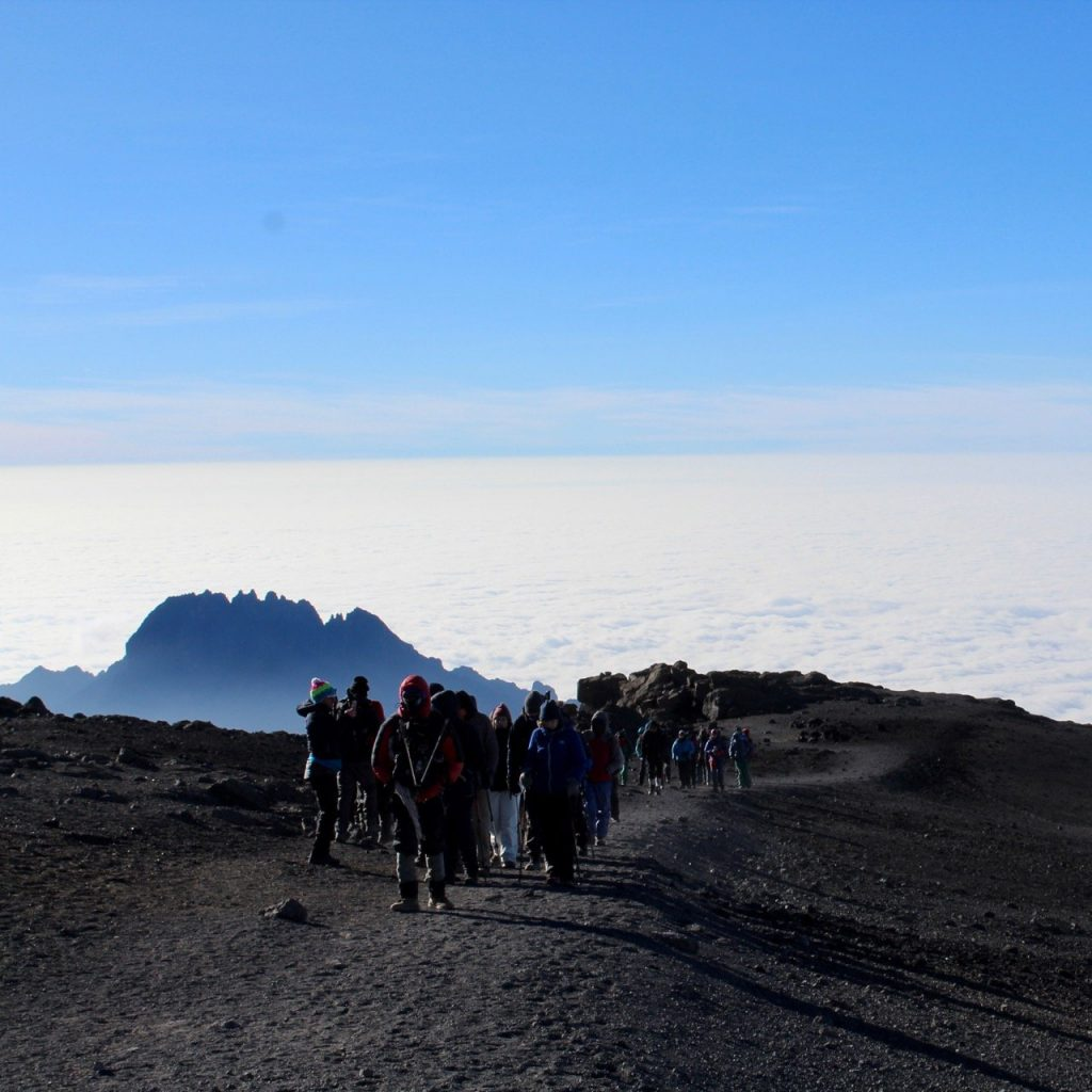 Hikers on Kilimanjaro high above the clouds on the path towards the summit.